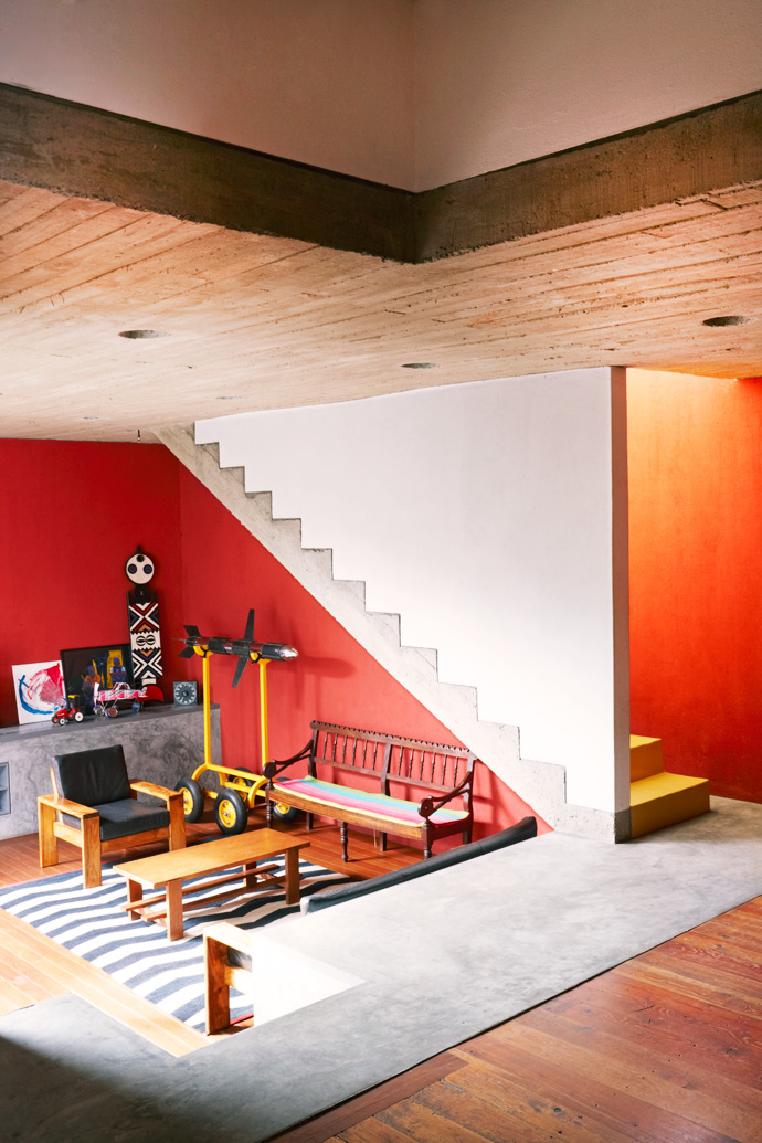 The Wolffs created a sense of drama inside the house using paint and plaster. By articulating the periphery with red paint, they have managed to make the space look larger than it is.