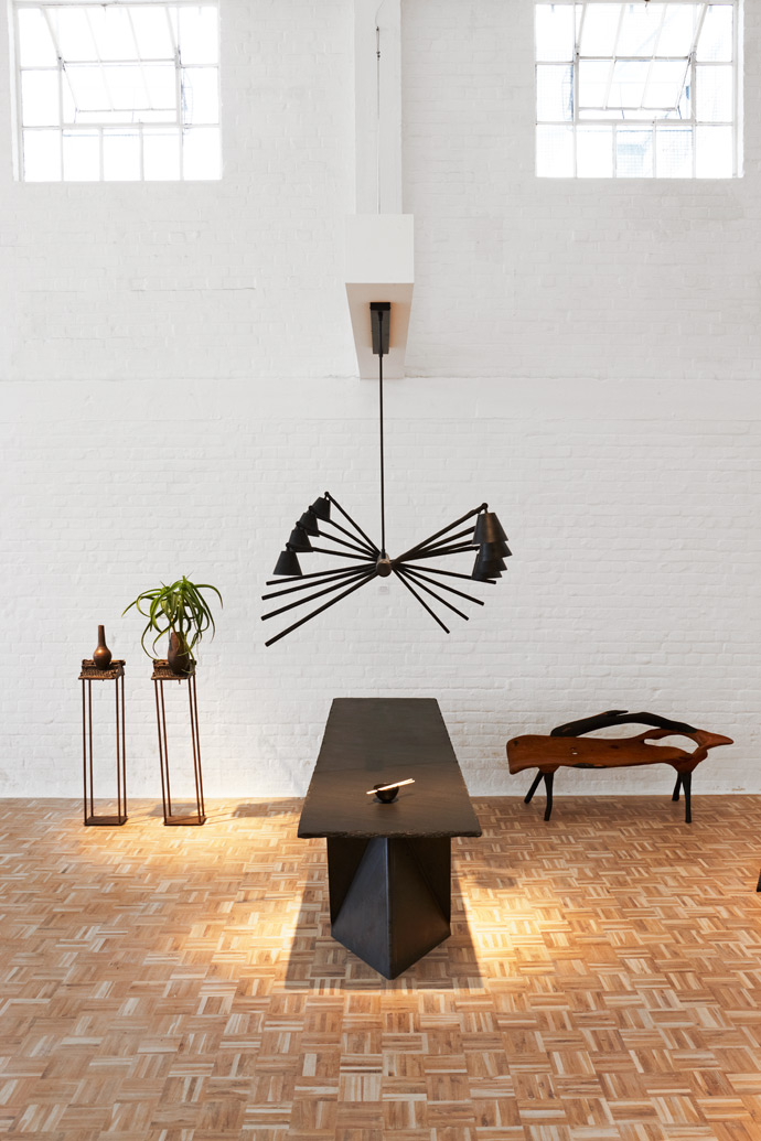 On the left, Vase Narrative I and II by Guydu Toit. A Haywire black ash chandelier by David Krynauw is suspended above Xandre Kriel's Vostable, with Michael MacGarry's Amicus Curiae on the tabletop. On the right is a Banc Bovidé byBabacarNiang.