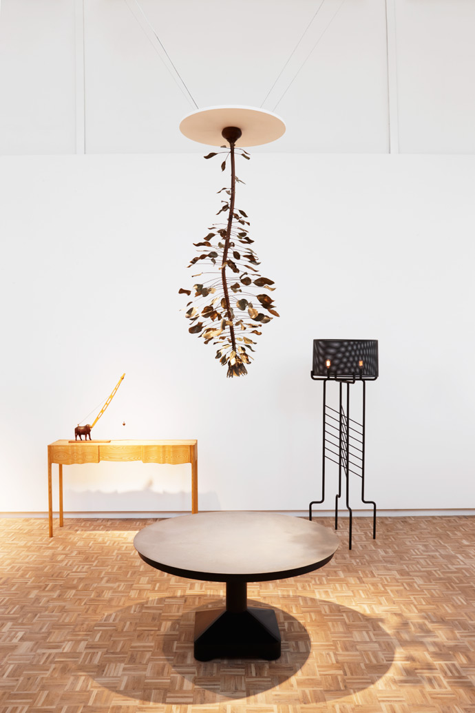 Against the wall is aLinen-fold table by Koop Design, with Still Mind Toy by Philippe Bousquet on top of it. On the right is a High Voltage standing lamp by Adam Court for OKHA. A Protea chandelier by Nic Bladen is suspended above Gregor Jenkin's Enduct table.