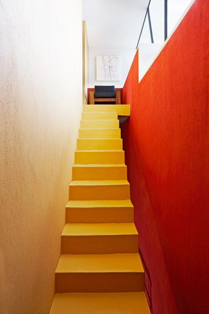 The yellow staircase leading up to the Wolffs' bedroom does not connect to the outside wall, leaving a gap for light to pass through from the large windows on the upper level.