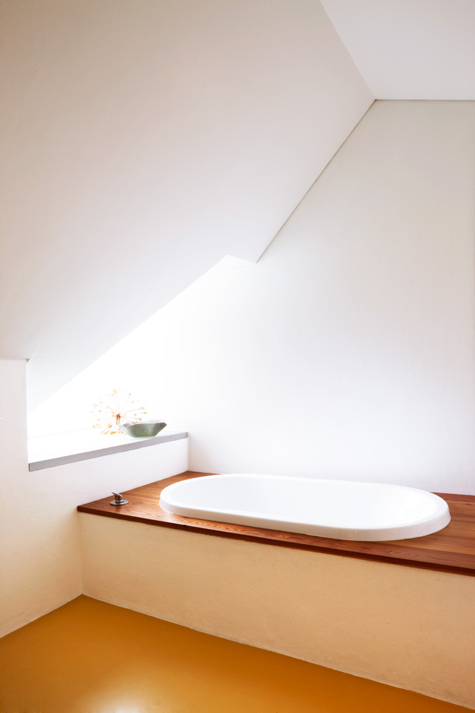 The Wolffs lowered the original ceiling of the Victorian house to create the extra space needed to accommodate their bedroom and upstairs bathroom. The simple bath is stylish without being pretentious