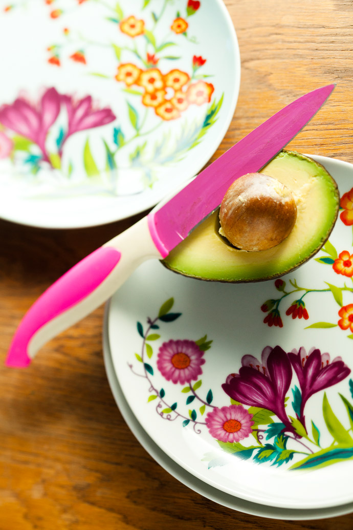 In summer, the family's avocado tree groans with fruit. The bright floral plates are from Woolworths and the shocking-pink knife belongs to a Maxwell & Williams range, available at Banks.