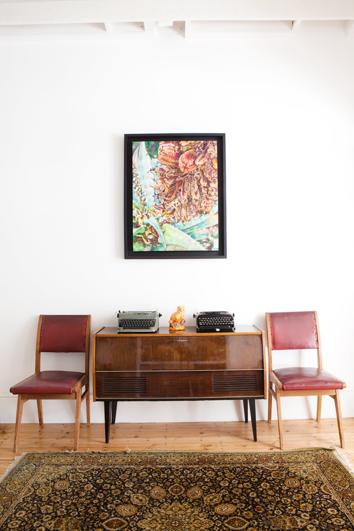 A painting by Claudia Gurwitz keeps company with a vintage radio, aMilnerton Flea Market find, and two chairs that are part of the house's original dining set, a gift from the previous owners.