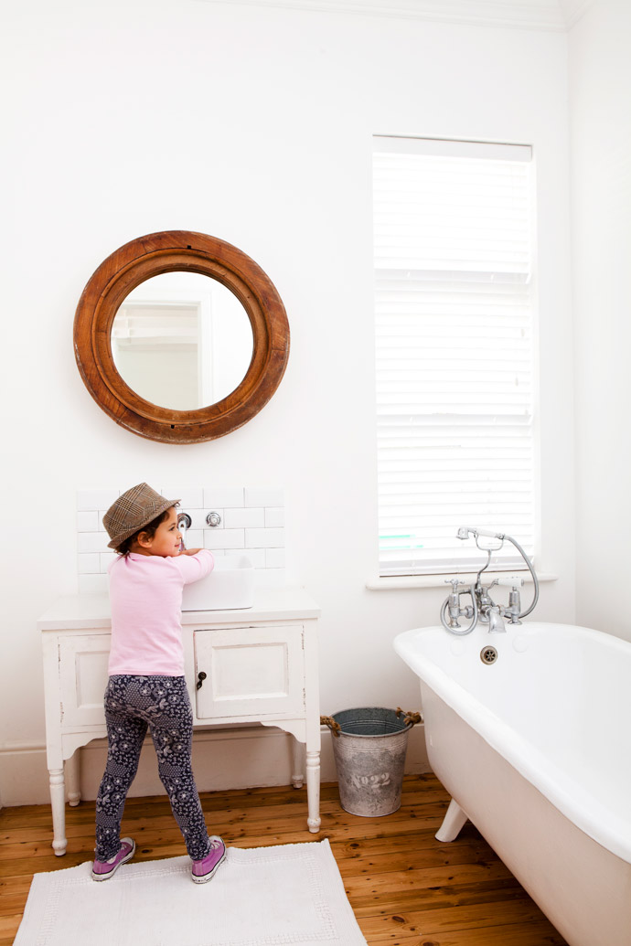 Mira washes her hands in the second bathroom. The striking mirror frame was this bathroom's original Oregon pine window frame. Cara had a wash basin made from a cabinet, another Wynberg find. The metro tiles are from Tilehaus.