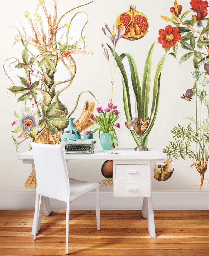 Cara's workspace doubles as a spare room. The Botanical wallpaper, from the Cara Saven Collection, was custom-designed. Perching on the small desk, custom-made by a carpenter in Woodstock, are two turquoise market-find vases flanked by a Lisa Firer work. The old typewriter is a prop used in a film by Marvin's company, the copper lamp is from Mr Price and the chair is from Coricraft.
