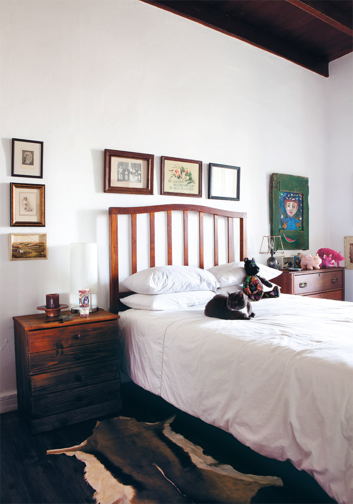 Afrikaner kitsch gives the spare bedroom an old-world feel. The painting on the green door above the chest of drawers on the right is by illustrator and artist Piet Grobler. The lamp was made by Peter's Dutch grandfather, an engineer, in Barberton. (Sagrys is lying on the bed.)