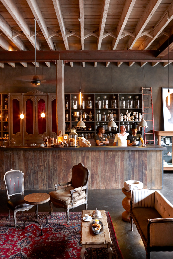 The bar and coffee counter behind which Prosper Dhlodhlo, Francois Irvine and Mandla Mkandla are standing is made of salvaged wood. APersian carpet offers asplash of colour against antique chairs, some upcycled and others bearing the markings ofhaving been battered by time and history.