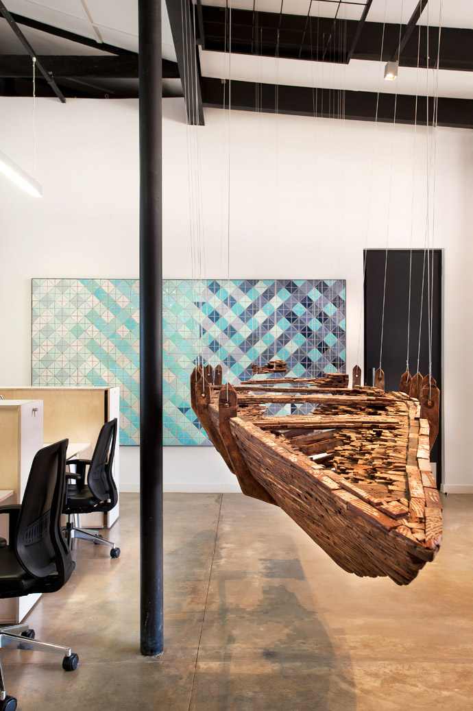 Artwork in the foreground: Emma Willemse, De[part], suspended boat sculpture made of reclaimed parquet floor blocks and nylon gut. Wall panel: Half Square ceramic tile installation, conceived by Matty Roodt and produced by Yellowwoods Art.