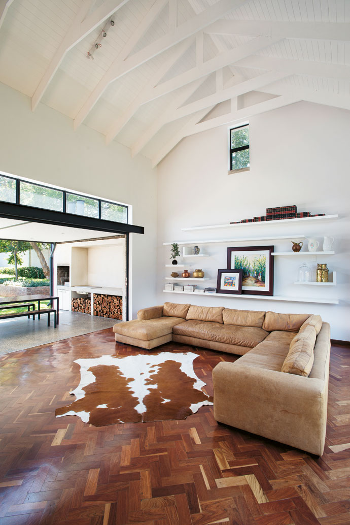 The double volume and open beams in the lounge make the room look much bigger than it is. Fold-away glass walls opposite allow good cross ventilation in summer and let in sunlight. Wood and leather add warmth to the otherwise predominantly whitedecor.