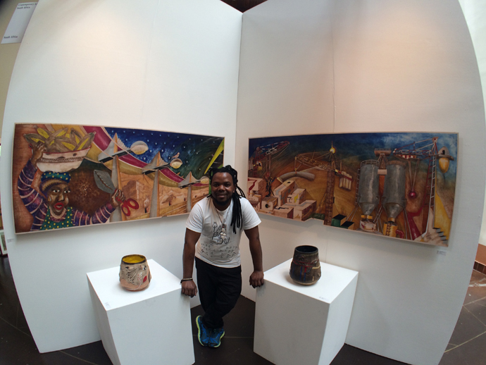 Andile standing at his booth with his new leather artworks hanging behind and his ceramic vases on the plinths.