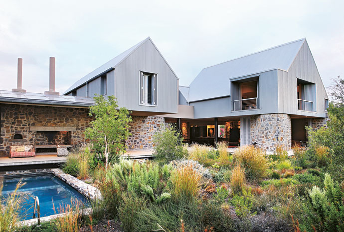 The house consists of four barn-like structures linked together with a series of stone walls.