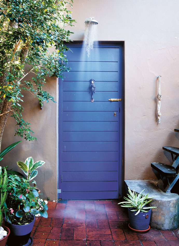 """Bold indigo frames the outdoor shower. The inviting doorway leads to a private servitude that Adam plans to reclaim and incorporate into the courtyard via a""""picturewindow""""."""