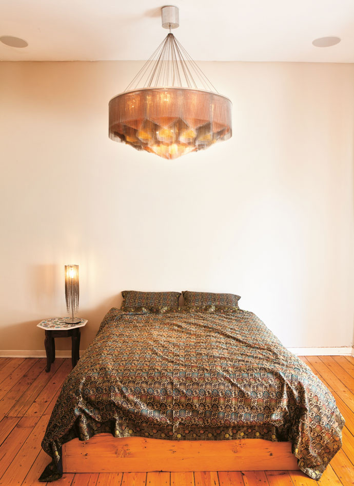 The bedroom is a minimal affair. Adam bought the bed linen on arecent trip to India. The colours and decorative patterns of the fabric speak to the Mandala No. 2 hanging above the bed.