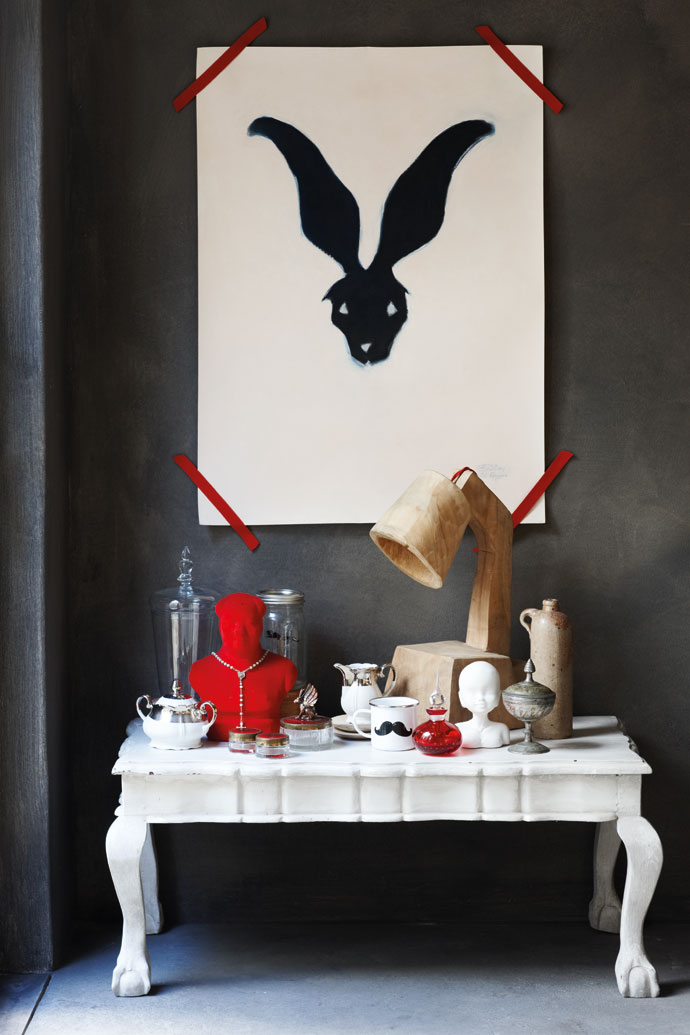 On the wall is an original charcoal drawing by Cape Town artist Brett Williams. The wooden lamp is a limited-edition carved piece by Liam Mooney and the rest of the pieces on the table are personal items.