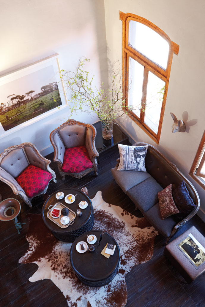 Most of the furniture and decor elements are personal items belonging to the owners. The framed photograph is by Frank Ellis and the white scatter cushion features a Flip Coaton illustration printed on fabric.