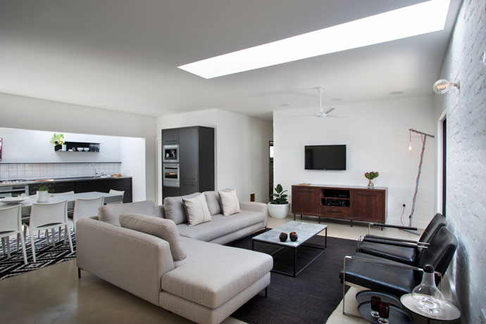 The couch in the open-plan lounge and kitchen area is from Weylandts, and the coffee table and corner lights were designed and made by Christo's company, Muse Contracts. The concrete flooring was done by his secondary company, Vloer. The couple opted for soft lighting and skylights rather than ceiling lights.