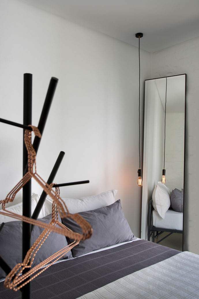 The mirror in the guest bedroom is a Muse Contracts design and the copper hangers were bought at a store in Marylebone, London. The bed is an old army cot, with bedding from Loads of Living. The bedside light is from Modernist.