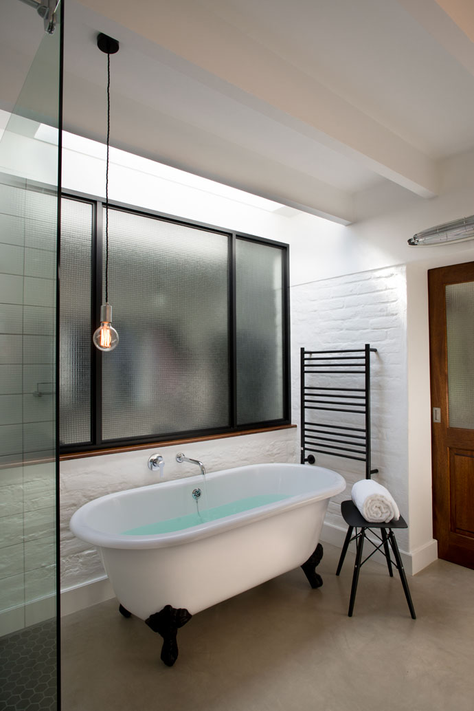 In the ensuite bathroom, the free-standing tub with its black feet gives a vintage feel with a contemporary twist. The skylight allows natural light into the room, and the bare-bulb pendant adds a romantic touch.