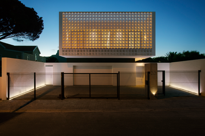 The mass of the floating box is counterbalanced on the street façade with a dramatic screen wall that casts interesting shadows throughout the day and creates an open-air terrace for the guest wing of the house.
