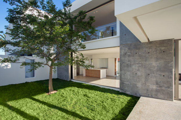 The living spaces on the ground floor and the bedrooms on the top floor overlook the central courtyard.