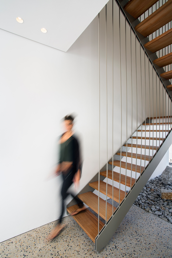 A steel-and-timber staircase is suspended from the ceiling bysteel rods.