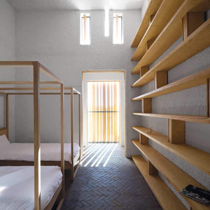 The open shelving in the bedroom is by Woodgrain. The glazing is left without window treatments, as the shutters screen the light. Asecond – concealed – sliding door darkens theroom at night.