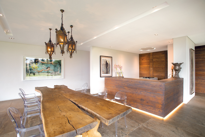"""The dining table is one of only two tables made from anold oak tree struck down by lightning; the owners say they """"begged it off the Everard Read Gallery"""". The Louis Ghost chairs are from Spazio. The artwork on the left is by Beezy Bailey and the one behind the kitchen counter by Deborah Bell."""