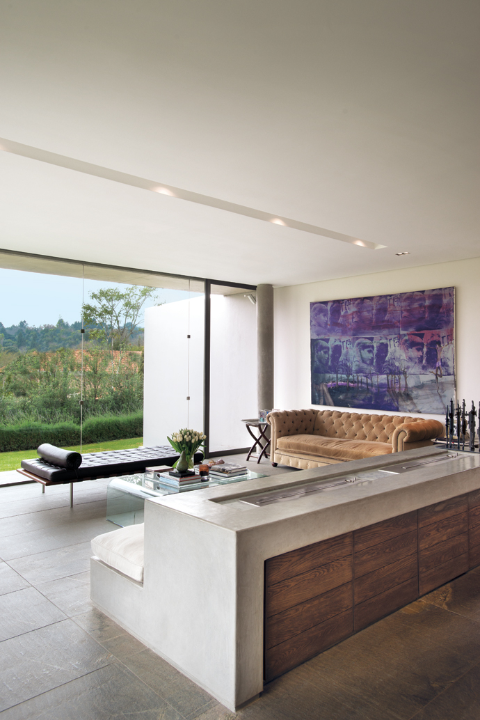 The homeowners opted to reuse some of their own furniture, such as the Mies van der Rohe Barcelona couch and the chesterfield made by Petite Designs, and wait for the opportunity to find special pieces. The artwork on the wall is by Beezy Bailey.