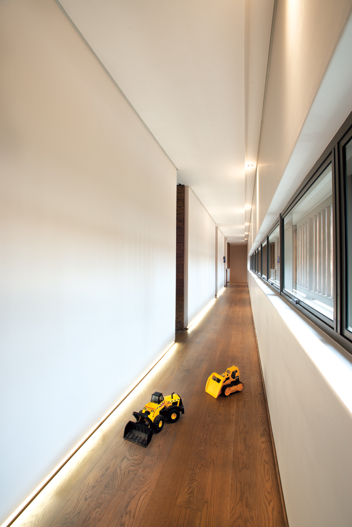 Three bedrooms lead off the long passage, which is lit by recessed floor-level LED lights.
