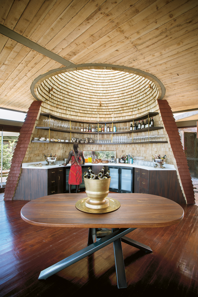 The armoire at the entrance of the guest area serves as an open bar. The table is by Prabh of DuMont Enterprises in Nairobi.