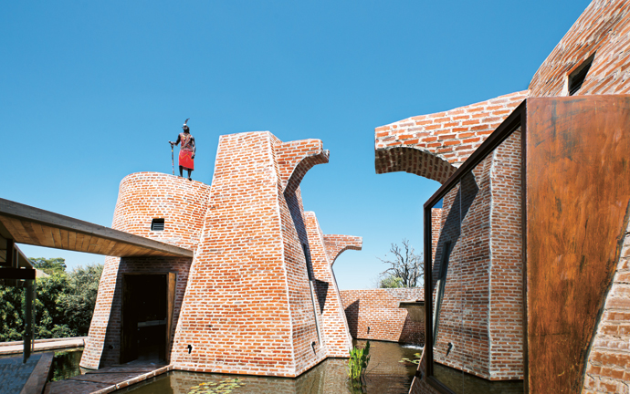 Architects Silvio Rech and Lesley Carstens understood the theatre demanded by a location like this in remote Africa. The imposing figure of Maasai naturalist John Peenko perched on the roof of the vestibule adds to the drama.