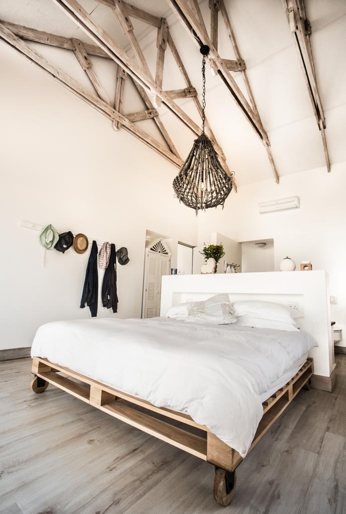 The bed and light fitting in the main bedroom are from Weylandts, and the coat hook by Peter Osborn Furniture. An open-plan bathroom is concealed behind the low wall at the head of the bed.