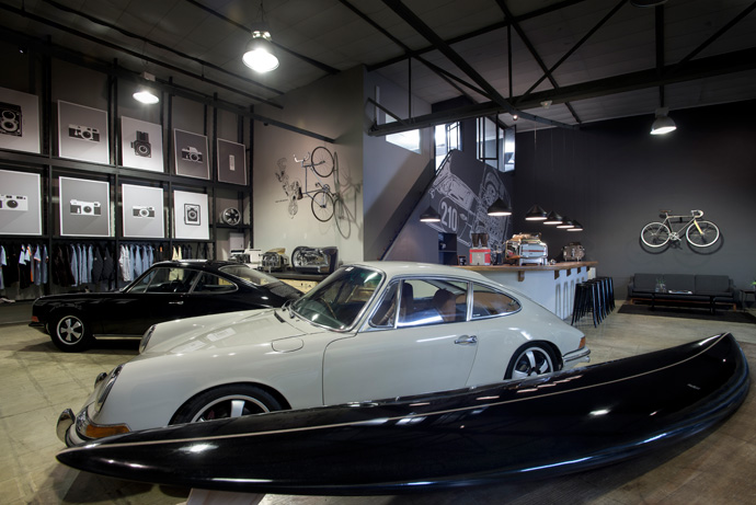 """In the foreground is a 1968 Porsche912 Weekend Racer and behind it a1971 Porsche911T. Classic and contemporary Faema coffee machines are on display alongside Dutchmann's """"Iconic Camera Poster Portfolio"""", comprising 10iconic film cameras that have made a remarkable contribution to photography."""
