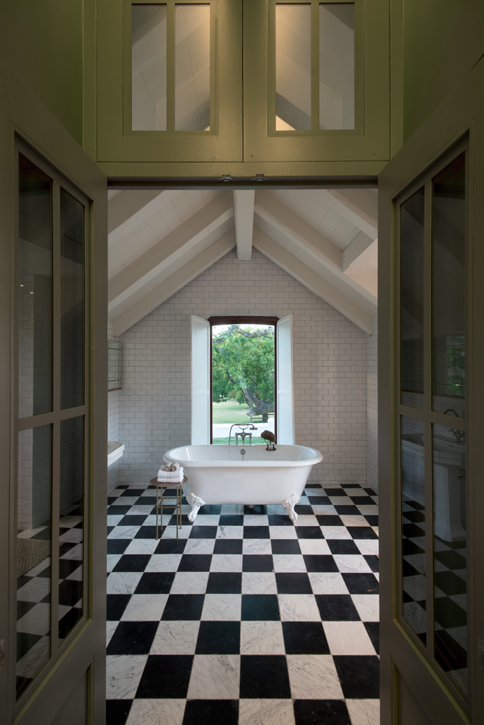 The spacious bathroom with a view features a magnificent freestanding bath from Victorian Bathrooms.