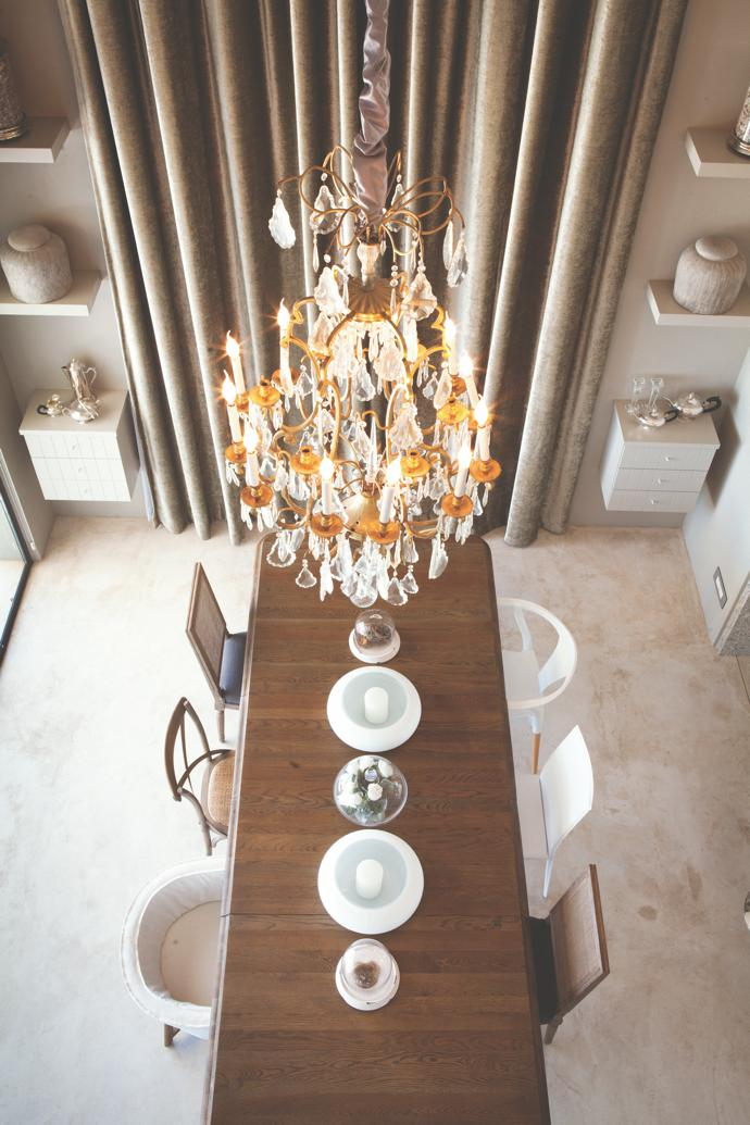 Viewed from the first-floor balcony, the dining area is dominated by anoak table from Block & Chisel. An eclectic collection of chairs mixes vintage withmodern.