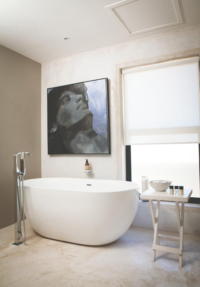 In a minimalist bathroom, apainting of aGrecian head dominates the silent space.