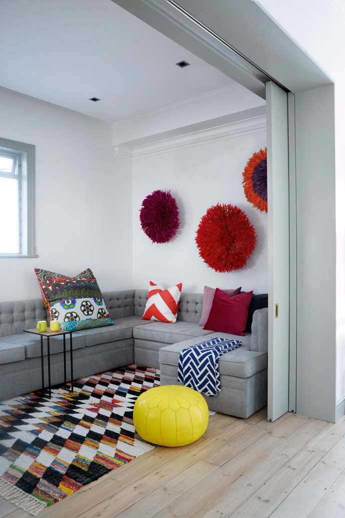 Bamiléké feather headdresses adorn one wall of the TVroom. The sofa is covered in Hertex grey velvet and the scatter cushions are from Big Blue. The yellow pouffe was specially imported by Moroccan Warehouse.