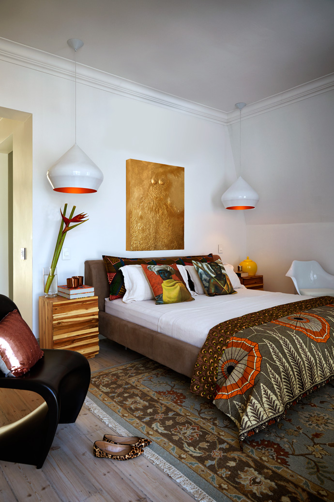 The colours in the master bedroom imbue the space with warmth. The bed is from Coricraft, the bedcover and large cushions are custom-made, the scatter cushions are from the Tretchikoff Project and the rug is from Gonsenhausers Fine Rugs. The artwork above the bed is by KayAlmitra.