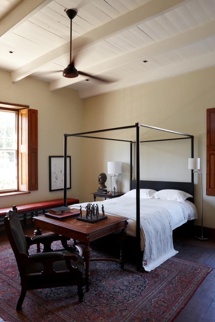 In the guest bedroom, a contemporary four-poster bed anchors the antique furniture and precious objects.