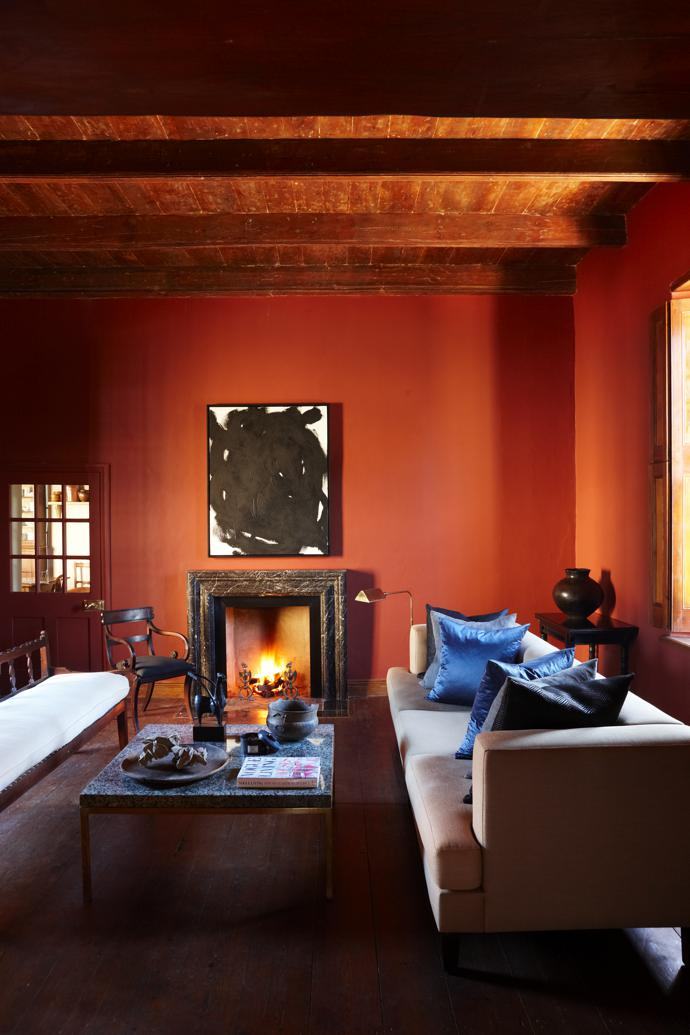 The sitting room has oxblood-red walls, shutters that keep the room cool in summer and a fireplace to heat it in winter. The painting above the fireplace is by Jacques.