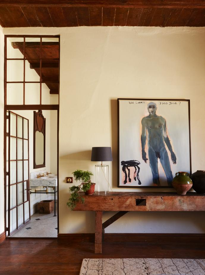 Glass-and-steel inner doors and transom windows allow for maximum light. This one leads from the master bedroom to the bathroom, which has a second door to allow for a good flow of energy. The painting is by Leon Vermeulen.