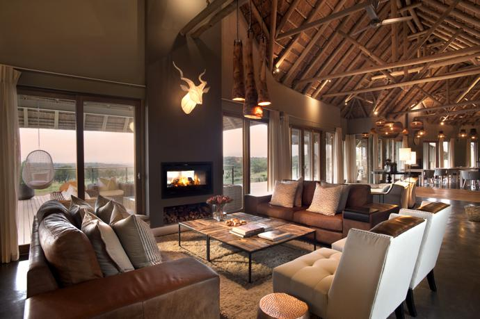 The lounges in the main lodge and the villa have two-way fireplaces that warm both inside and outside spaces. Leather couches are from Sevens and chairs from @home. The coffee table is from Weylandts and the wall-mounted Kudu Trophy light from Moonlight & Magic.
