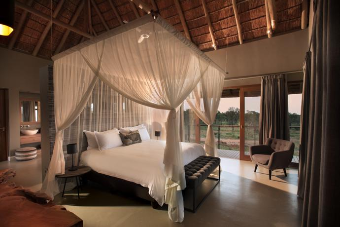 The rooms are designed and decorated for comfort and views. The main villa's lofty master bedroom opens onto a private deck with views across the waterhole and bush. The chair is from @home and the settee is by Sutherlands Home Furnishing.