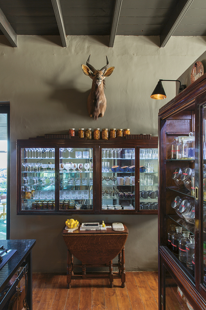 Etienne's enormous collection of glass stemware, which he insists be used, is displayed in illuminated vintage display cabinets.