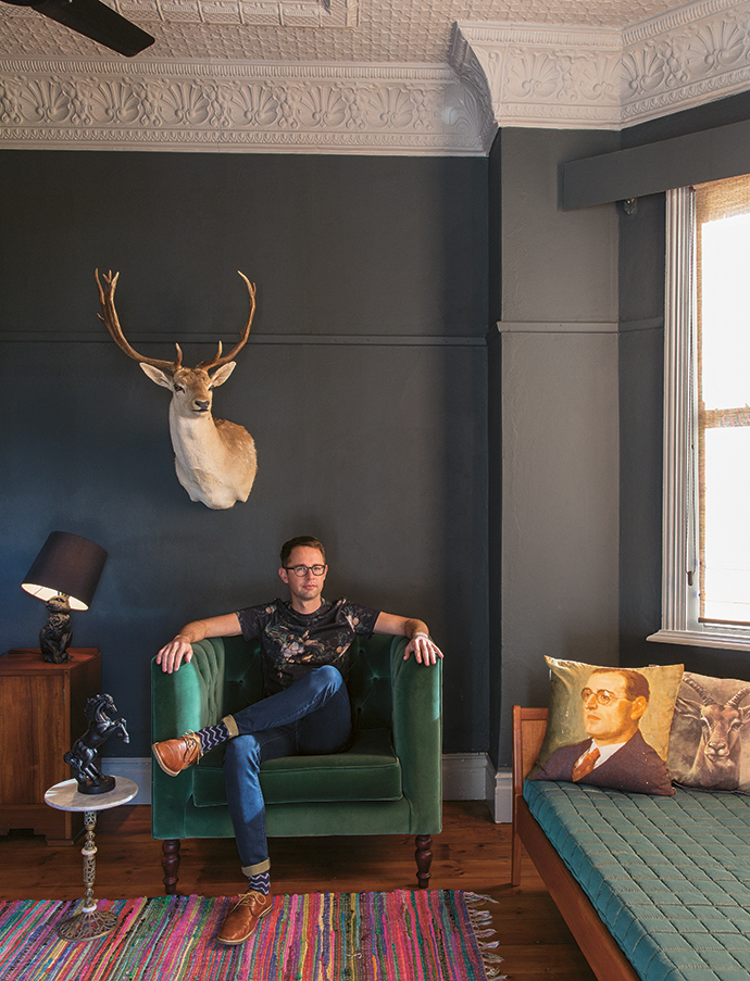 "Etienne, sitting in his bedroom underneath a reindeer head. The entire house is an eclectic tribute to nature. Says Etienne, ""I will never kill an animal for the purpose of taxidermy, so all my stuffed trophies have been recycled from dusty garages and storerooms all over the Western Cape, or bought via Gumtree or at Cash Crusaders."""