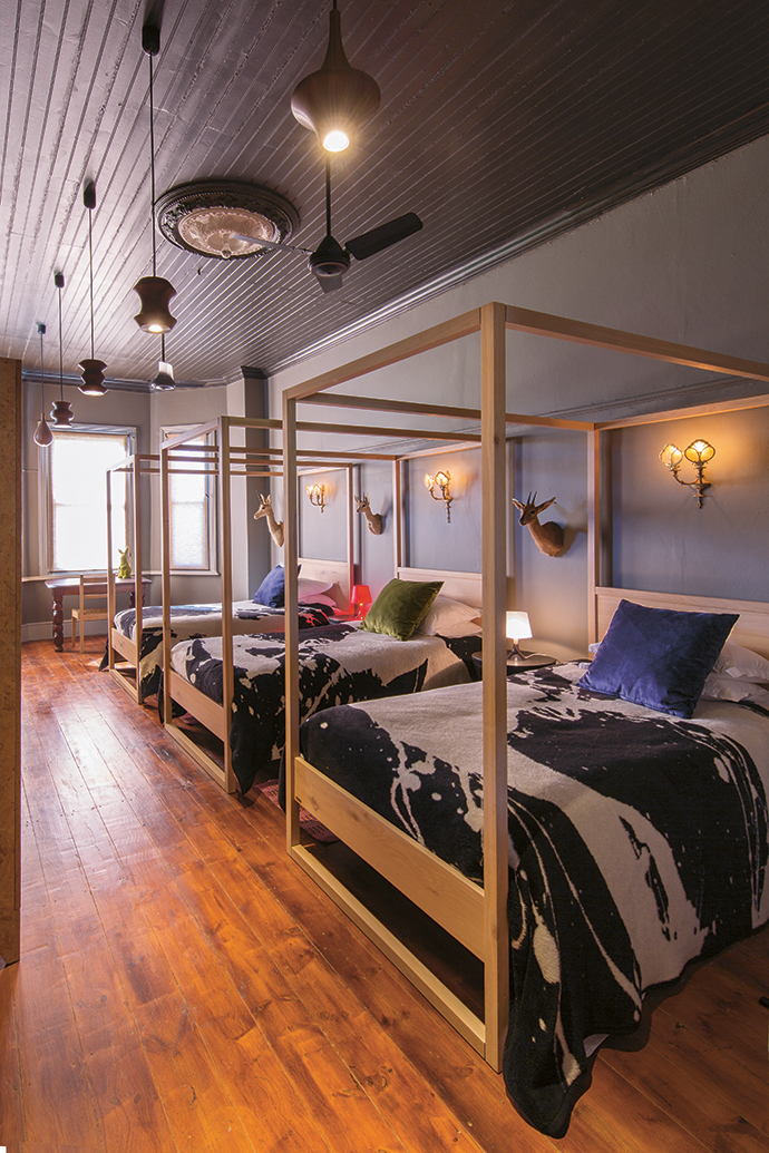 Etienne calls this bedroom (for all his single friends) the dormitory. Each of the fourposter beds has its own Queen Anne cupboard for clothes and a bedside table and lamp for reading. The pendant lights are by Porky Hefer and the blankets by Kurt Pio for Mr Price.