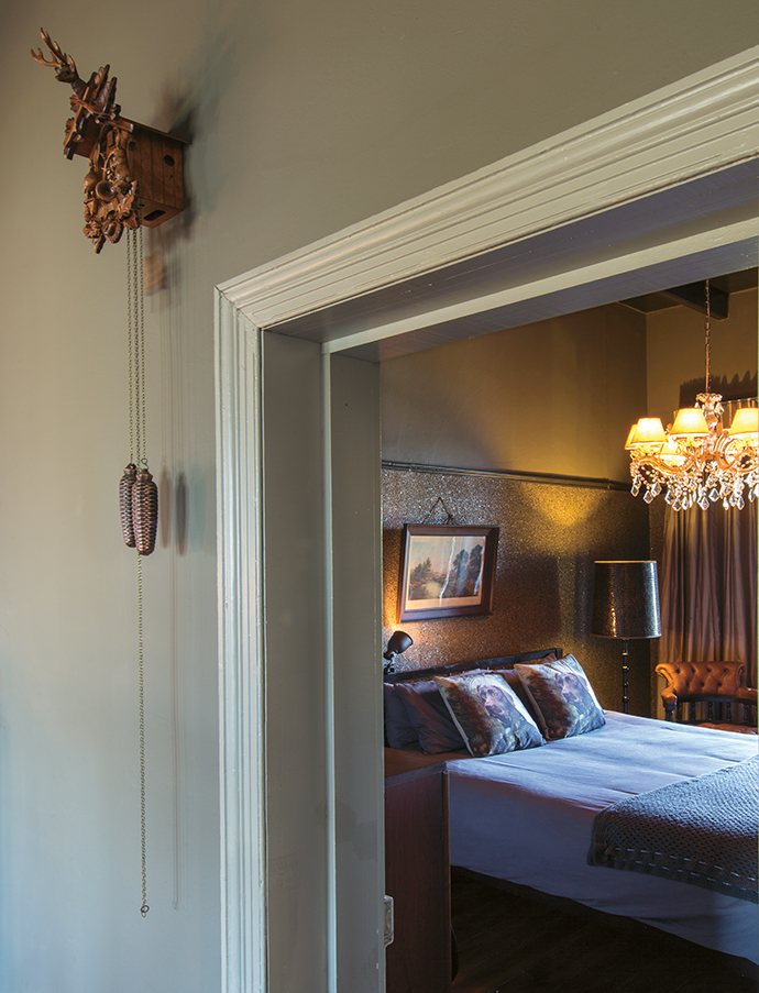 The intimate guest bedroom is papered with glittering textured wallpaper. The chandelier came with the house.