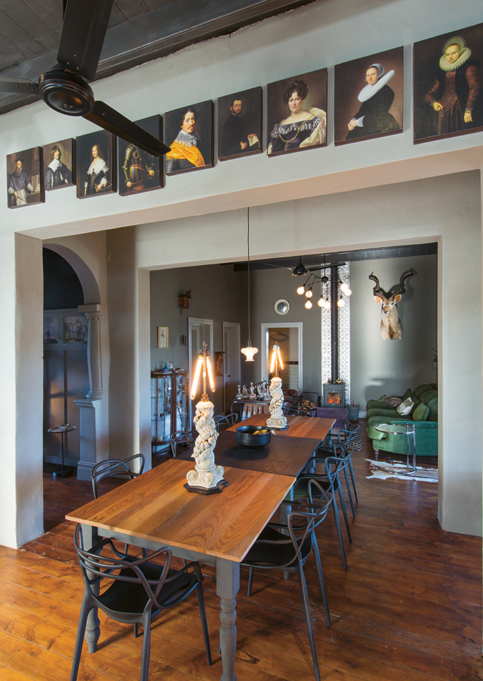 The dining area, with a large custom-made table and Kartell Masters chairs, is situated between the kitchen and the seating area with a fireplace.