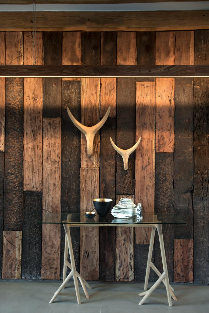 The reclaimed sleeper wood panels were done by Dajaza Houtwerk. The nguni heads are by Vogel, the Umthi glass server by Meyer von Wielligh for GDF Design Lab, the vases by Lisa Firer Design at Kim Sacks Gallery, and the bronze bowls from Bronze Age.