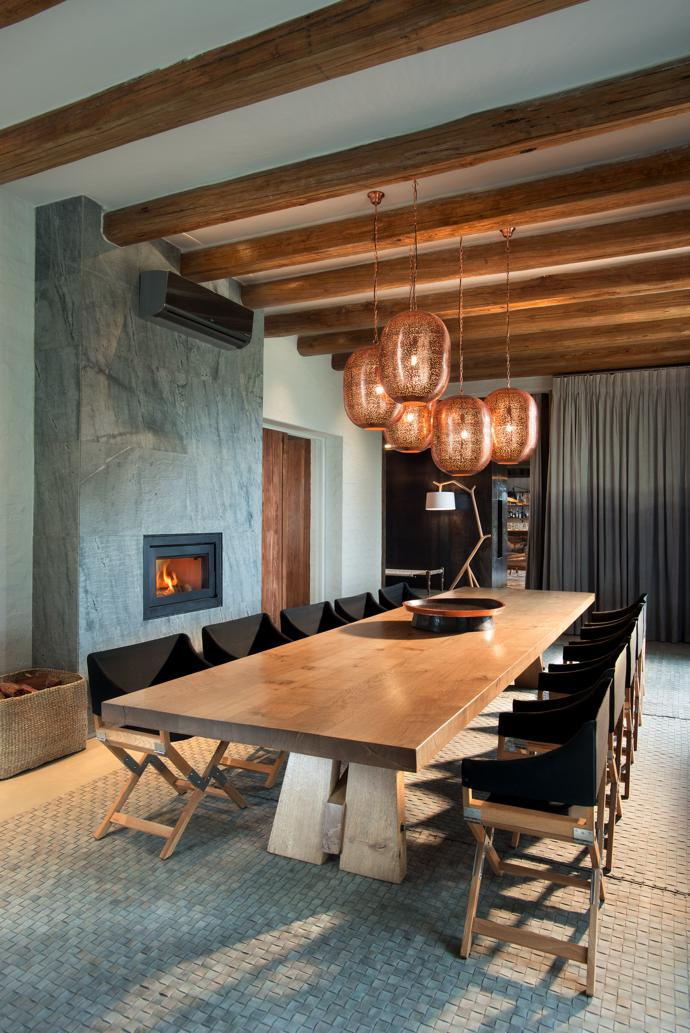 The open-plan dining room is warmed by aCanature wood stove and lit by copper pendant lights from Tusker Trading. TheBloukrans dining table is from Pierre Cronje and the DePadova Sundance chairs from Generation Design. The woven leather rug was made by Papilio.